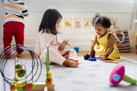 Bambini piccoli che giocano con i giocattoli nella stanza dei giochi