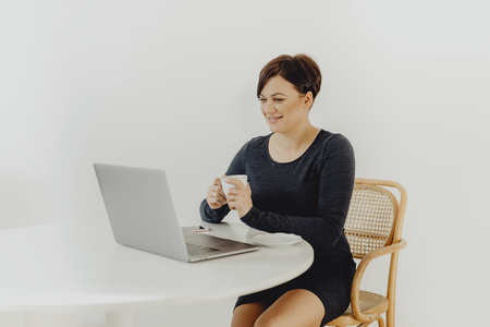Positive woman with a cup of tea telecommuting Stock Photo