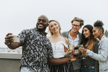 Diverse group of friends taking a selfie at a rooftop party