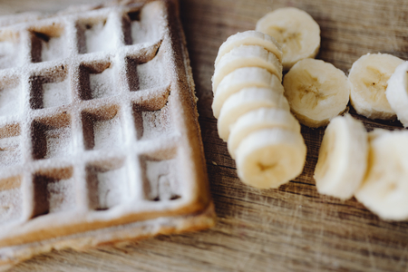 Waffle and slices of banana on a wooden tray