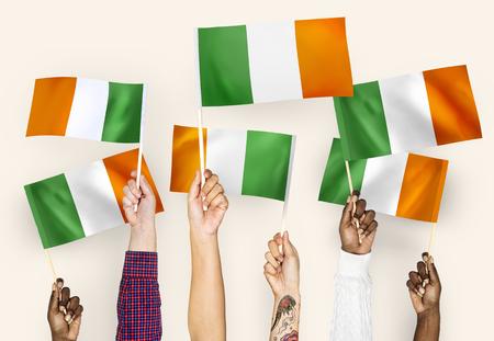 Hands waving flags of Ireland