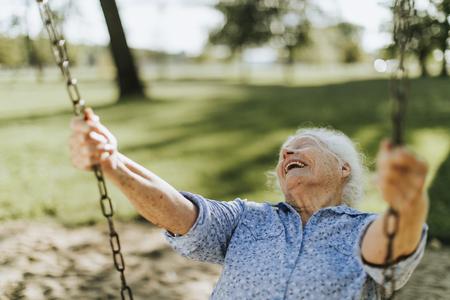 Cheerful senior woman sur une balançoire dans une aire de jeux