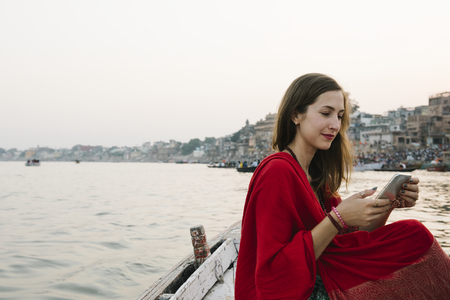 Western woman on a boat texting from the River Ganges