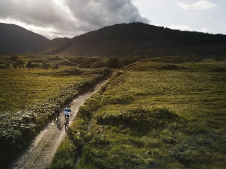 Coppia in bicicletta lungo una strada nelle Highlands scozzesi Archivio Fotografico