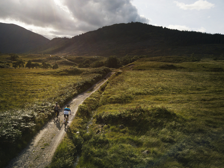 Couple cycling down a road in the Scottish Highlands 免版税图像 - 117116073