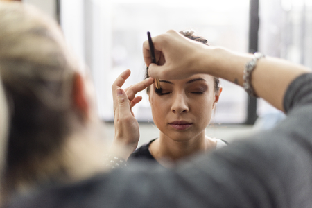 Makeup artist applying eyeshadow onto model Stock Photo