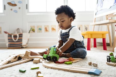 Ragazzino sveglio che gioca con un giocattolo del treno della ferrovia