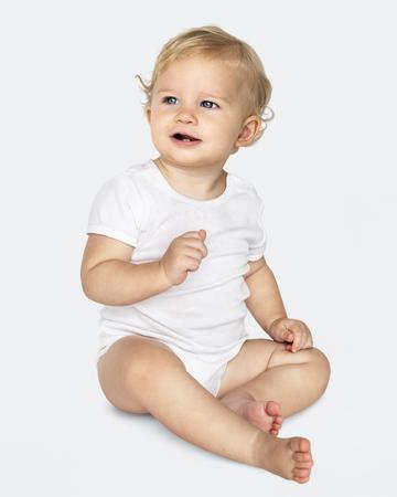 Bebé sentado en el suelo en un estudio.