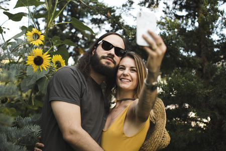 Couple taking a selfie with sunflowers