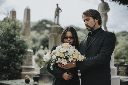 Couple grieving their loss at the cemetery