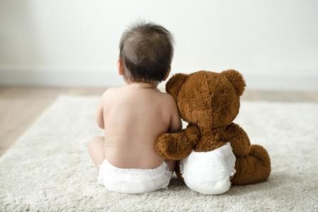 Detrás de un bebé con un osito de peluche