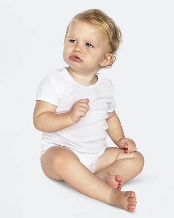 Baby sitzt auf dem Boden in einem Studio Standard-Bild
