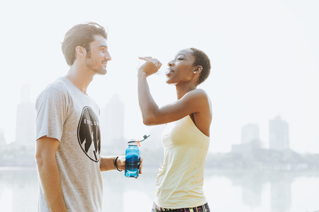 Fitness couple drinking water after workout