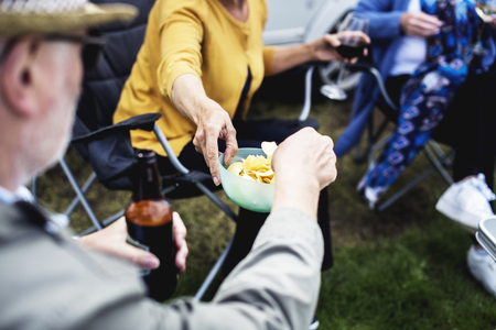People passing around a bowl of chips