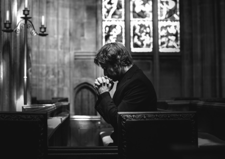 Lonely Christian man praying in the church Stock Photo - 117605723