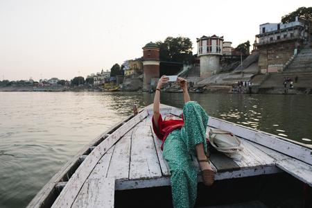 Western woman lying on a boat taking selfies in Varanasi