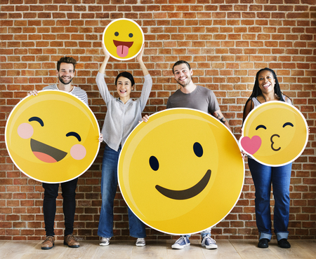 Diverse people holding positive emoticons 写真素材