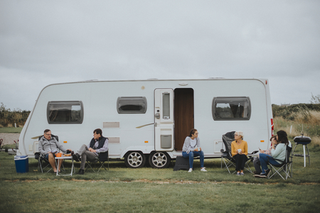 Group of people sitting outside a trailer