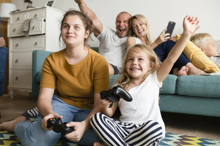Sisters playing a video game on the floor