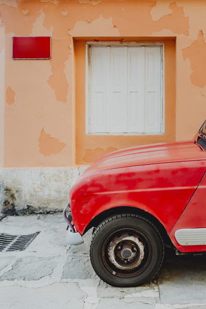 Vintage red car parked by an orange building Stock Photo