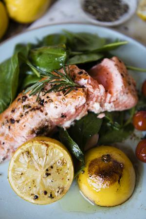 Grilled salmon filet with fresh greens Фото со стока