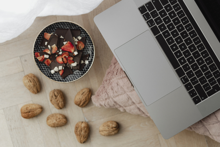 Dark chocolate brittle and walnuts on a wooden floor next to a laptop