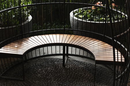 Fenced curved wooden seating in the garden
