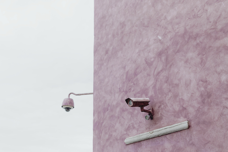 Pink wall with a CCTV Stock Photo