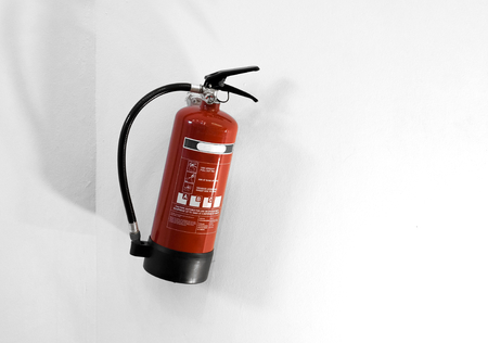 Red fire extinguisher on a white wall