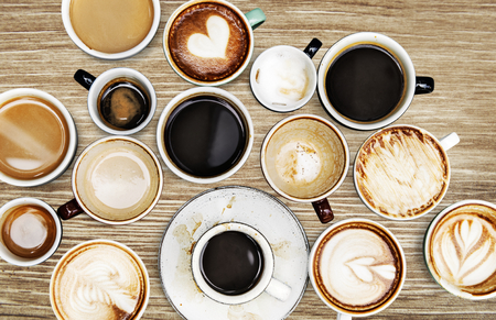 Assorted coffee cups on a wooden table Imagens