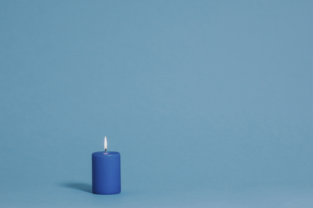Burning candle in blue color 版權商用圖片
