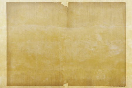 Blank grunge brown paper on a yellow wall