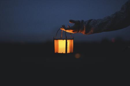 Hand holding a lantern in the dark 스톡 콘텐츠