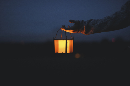 Hand holding a lantern in the dark Stock Photo
