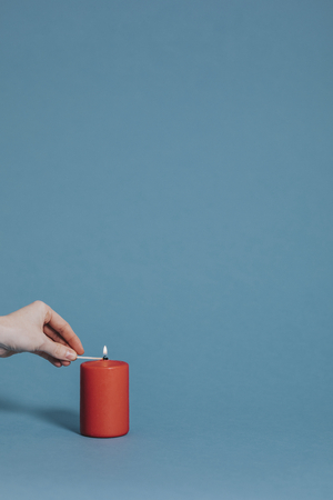 Woman lighting a red candle Stock Photo - 118637116