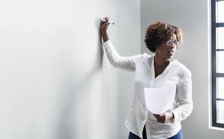 Schwarze Frau schreibt auf einem Whiteboard