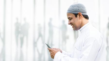 Muslim man using a phone