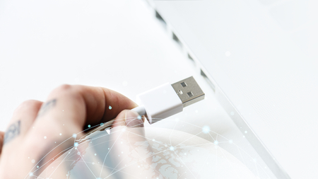 Hand connecting a USB cable to a laptop