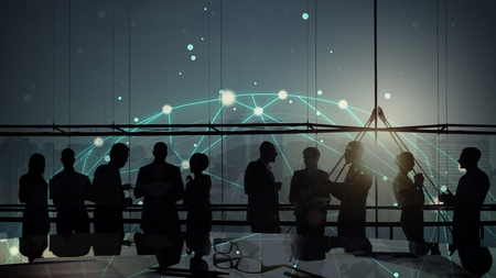 Silhouetted business people meeting in a boardroom Banco de Imagens