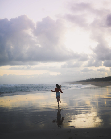 Rear view of woman running on a coast
