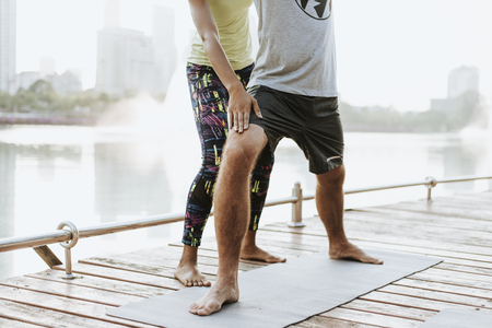 Couple doing a yoga in a park Stock Photo
