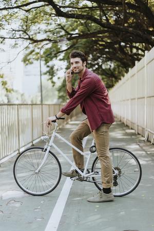 Young caucasian man circling at park and using mobile phone