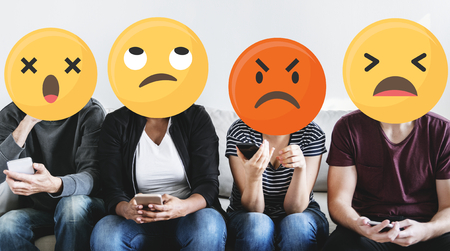 Diverse people with negative emoticons using mobile phones