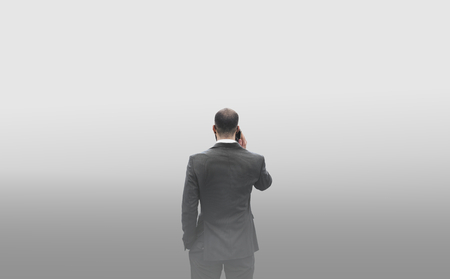 Rear view of a businessman talking on the phone in a smog