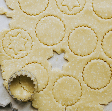 Raw cookies being cut with a star cookie cutter