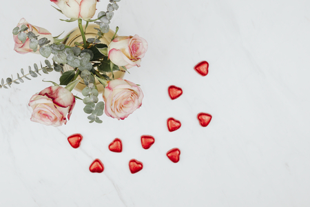 Valentine's rose bouquet with red chocolate hearts on a white marble background
