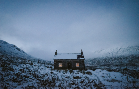 House covered with snow on a misty day