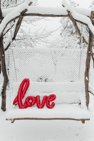 Red love balloon word on a snowy swing