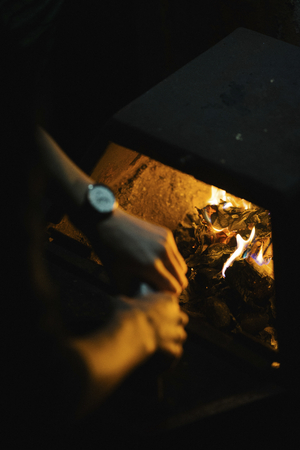 Man setting a fire in a fireplace