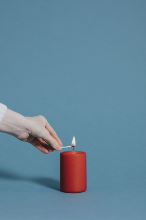 Woman lighting a red candle